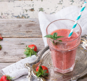Glass of red strawberry smoothie with chia seeds, served with retro cocktail tube, fresh mint and strawberries over wooden table