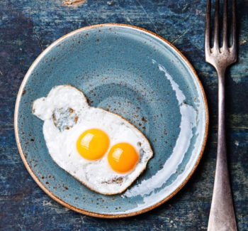Traditional breakfast eggs on blue background